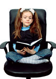 Girl reading a book in chair Royalty Free Stock Images