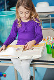 Girl Reading Book In Classroom Stock Image
