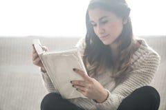Girl reading a book closeup on the sofa Stock Photo