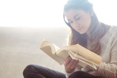Girl reading a book closeup on the sofa Royalty Free Stock Image