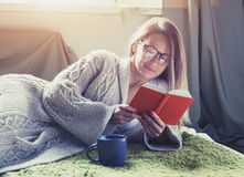 Girl reading book with coffee lying in bed Royalty Free Stock Images