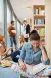 Girl reading book in college library. Girl reading book with group of students discussing in library Stock Images