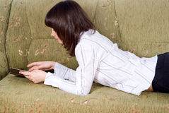 Girl reading a book on the couch Royalty Free Stock Photography
