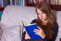 Girl reading a book on the couch Royalty Free Stock Photo