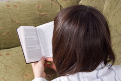 Girl reading a book on the couch isolated Royalty Free Stock Photography
