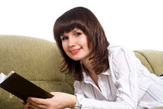 Girl reading a book on the couch isolated Stock Image