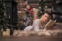 Girl reading a book in a cozy home atmosphere near the fireplace royalty free stock images