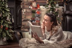 Girl reading a book in a cozy home atmosphere near the fireplace stock images
