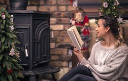 Girl reading a book in a cozy home atmosphere near the fireplace stock photos