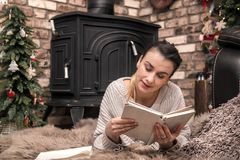 Girl reading a book in a cozy home atmosphere near the fireplace royalty free stock photography
