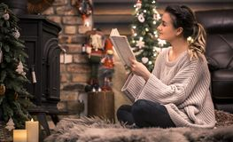 Girl reading a book in a cozy home atmosphere near the fireplace. The concept of home rest royalty free stock photo