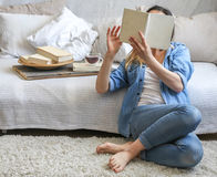 Girl reading a book in a cozy room Stock Photo