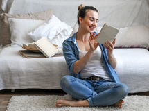 Girl reading a book in a cozy room Royalty Free Stock Images