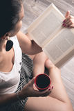 Girl reading a book with a cup of coffee. Sitting on the floor Royalty Free Stock Photography