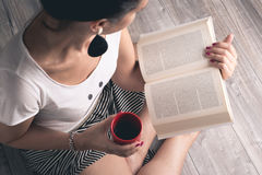 Girl reading a book with a cup of coffee Royalty Free Stock Photography