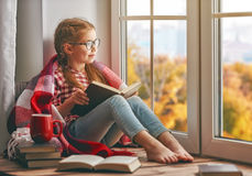 Girl reading a book. Cute child girl sitting by the window and reading a book in room at home. Beautiful autumn nature Royalty Free Stock Photos