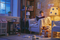 Girl reading a book. Cute little child girl reading a book under a lamp. Kid girl sitting in armchair near window in a dark moonlit night Royalty Free Stock Photo