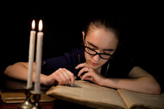 Girl reading book in dark library Stock Images