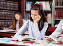 Girl Reading Book At Desk With Friends. Teenage girl reading book at table with friends in school library Royalty Free Stock Photo