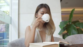 Girl reading book and drinking coffee. Asian girl reading book and drinking coffee stock video footage
