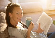 Girl reading book and drinking coffee on sofa Royalty Free Stock Photography