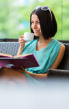 Girl reading book drinks coffee at the bar Royalty Free Stock Photo