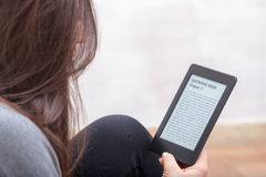 Girl is reading a book with an e-book reader. Brunette GIrl is focused reading an electronic book with her Ebook Reader. The text on the ebook reader is an lorem royalty free stock photos
