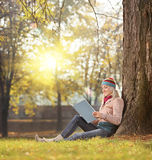 Girl reading a book and enjoying the sunny day in a park seated Stock Photos