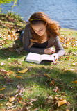 Girl reading book among fall leaves. Girl reads book for school in fall scene while laying down in the leaves and grass stock image