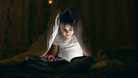Girl reading book with a flashlight under the covers at night stock video