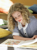 Girl Reading Book On Floor In Classroom Stock Image