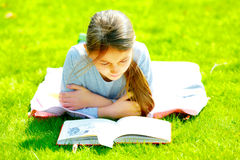 Girl reading  book on the grass Royalty Free Stock Photo