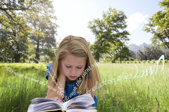 Girl reading a book in the grass Royalty Free Stock Images