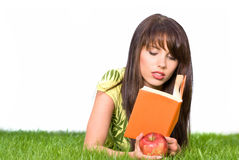 Girl reading book in the grass Royalty Free Stock Photos