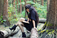 Girl reading a book in the green forest Royalty Free Stock Images