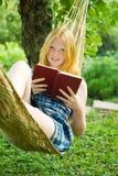 Girl reading book on hammoc Royalty Free Stock Photo
