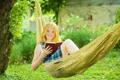 Girl reading book on hammock stock photos