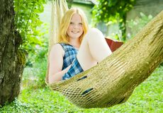Girl reading book on hammock Stock Image