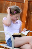 Girl reading book has questions. A little young girl scratching her head while reading her book. Shallow depth of field Stock Photography