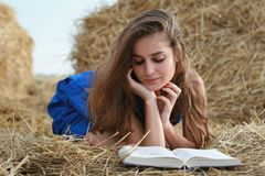 Girl reading book on hay Royalty Free Stock Images