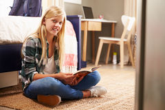 Girl reading a book in her bedroom Stock Photography