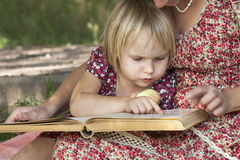 Girl reading a book on his mother's lap Royalty Free Stock Photo