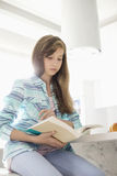 Girl reading book at home Stock Image