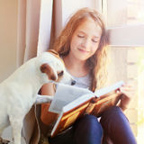 Girl reading book at home. Child with dog reading book at home. Girl with pet sitting at window at read Stock Image