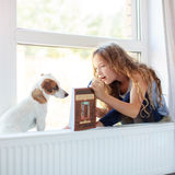 Girl reading book at home. Child with dog reading book at home. Girl with pet sitting at window at read Stock Photo