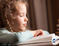 Girl reading book at home Stock Images
