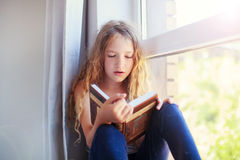 Girl reading book at home Stock Photos