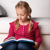 Girl Reading Book At Home Royalty Free Stock Photos