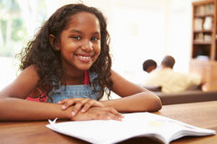 Girl Reading Book For Homework At Table Stock Image