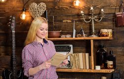 Girl reading book in house of gamekeeper. Girl in casual outfit in wooden vintage interior enjoy poetry. Vintage concept. Lady blonde on smiling face in plaid Stock Image
